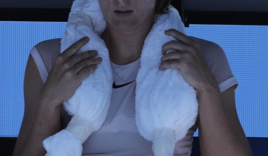 Russia's Maria Sharapova uses a cool towel during a break while playing Latvia's Anastasija Sevastova during their second round match at the Australian Open tennis championships in Melbourne, Australia, Thursday, Jan. 18, 2018. (AP Photo/Vincent Thian)