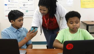 In a Thursday, Jan. 11, 2018 photo, Deyonna Davis, center, teacher and the sponsor of the coding club helps sixth graders Hemant Pacha, left, 11, and Mikey Shands, 11, work on their phones and computers where they attend a coding club at Barbara Bush Middle School in Irving, Texas. They both create an app for games and Mikey has his own YouTube channel. Hemant wants to be a doctor and a part-time video game designer and Mikey wants to be a cartoon animator. (David Woo/The Dallas Morning News)