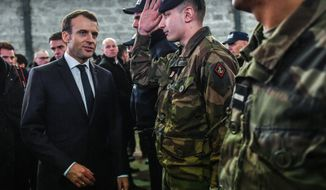 "French President Emmanuel Macron speaks with soldiers during his visit to Calais, northern France, Tuesday, Jan.16, 2018. Macron traveled Tuesday to the epicenter of France's migrant crisis, the northern port of Calais, to lay out a ""humane and tough"" immigration policy that involved better behavior by security forces and closer cooperation with Britain. (Denis Charlet/Pool via AP)"
