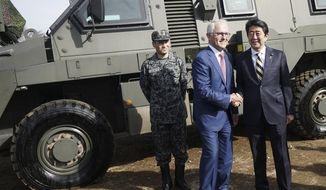 Australian Prime Minister Malcolm Turnbull, center, and Japanese counterpart Shinzo Abe, right, shake hands in front of a Bushmaster Protected Mobility Vehicle at Narashino Exercise Area in Funabashi, Chiba Prefecture, east of Tokyo Thursday, Jan. 18, 2018. (AP Photo/Eugene Hoshiko)