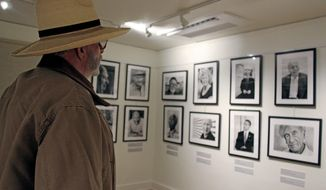 Pete Stapler, a resident of El Valle de Arroyo Seco, attends the opening of the Nobel Heroes Portraits exhibit by Peter Badge at the Los Alamos History Museum on Friday, Jan. 12 2018. The exhibit is open to the public until April 27, and features portraits of nearly 40 Nobel Prize winners. (Michaela Meaney /Santa Fe New Mexican via AP)