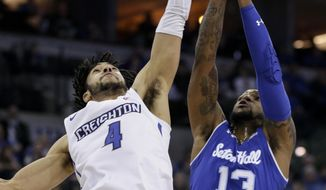 Creighton's Ronnie Harrell Jr. (4) beats Seton Hall's Myles Powell (13) to a rebound during the first half of an NCAA college basketball game in Omaha, Neb., Wednesday, Jan. 17, 2018. (AP Photo/Nati Harnik)