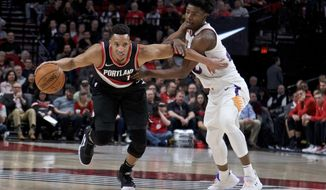 Portland Trail Blazers guard Evan Turner, left, dribbles past Phoenix Suns forward Josh Jackson during the first half of an NBA basketball game in Portland, Ore., Tuesday, Jan. 16, 2018. (AP Photo/Craig Mitchelldyer)