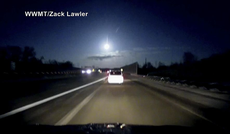 In this late Tuesday, Jan. 16, 2018, image made from dashcam video, a brightly lit object falls from the sky above a highway in the southern Michigan skyline. (Zack Lawler/WWMT via AP)