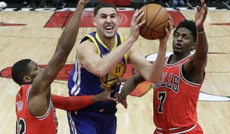 Golden State Warriors' Klay Thompson (11) shoots between Chicago Bulls' Kris Dunn (32) and Justin Holiday, right, during the second half of an NBA basketball game Wednesday, Jan. 17, 2018, in Chicago. The Warriors won 119-112. (AP Photo/Charles Rex Arbogast)