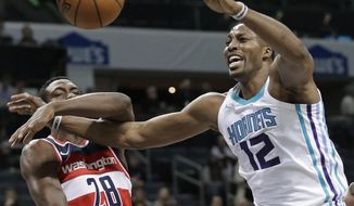 Charlotte Hornets' Dwight Howard (12) is fouled by Washington Wizards' Ian Mahinmi (28) during the first half of an NBA basketball game in Charlotte, N.C., Wednesday, Jan. 17, 2018. (AP Photo/Chuck Burton)