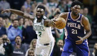 Philadelphia 76ers' Joel Embiid (21) beats Boston Celtics' Jaylen Brown (7) to the ball during the fourth quarter of an NBA basketball game in Boston, Thursday, Jan. 18, 2018. (AP Photo/Michael Dwyer)