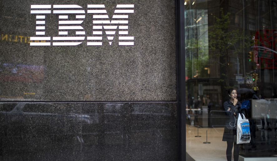 In this Wednesday, April 26, 2017, photo, a woman looks out from the lobby next to the logo displayed on the IBM Building in New York. On Thursday, Jan. 18, 2018, IBM Corp. reports financial results. (AP Photo/Mary Altaffer)