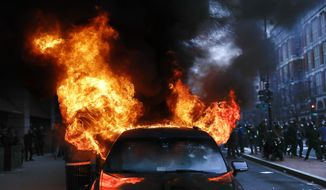FILE - In this Jan. 20, 2017, file photo, a parked limousine burns during a demonstration after the inauguration of President Donald Trump in downtown Washington. The U.S. government announced on Thursday that it is abandoning its prosecution of more than 120 defendants charged with crimes over their involvement in violent protests on the day of Donald Trumps inauguration one year ago. (AP Photo/John Minchillo, File)