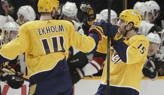 Nashville Predators defenseman Mattias Ekholm (14), of Sweden, celebrates with right wing Craig Smith (15) after Smith scored the winning goal against the Arizona Coyotes during the shootout in an NHL hockey game Thursday, Jan. 18, 2018, in Nashville, Tenn. The Predators won 3-2. (AP Photo/Mark Humphrey)