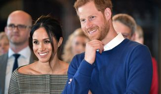 Britain's Prince Harry and Meghan Markle watch a performance Cardiff Castle in Cardiff, Wales, Thursday, Jan. 18, 2018. During their tour, Prince Harry and Ms. Markle will hear performances from musicians and poets, meet sportsmen and women, and see how organisations are working to promote Welsh language and cultural identity. (Ben Birchall/Pool Photo via AP)