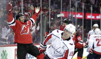 New Jersey Devils defenseman Andy Greene, left, celebrates his goal against the Washington Capitals during the second period of an NHL hockey game Thursday, Jan. 18, 2018, in Newark, N.J. (AP Photo/Julio Cortez)