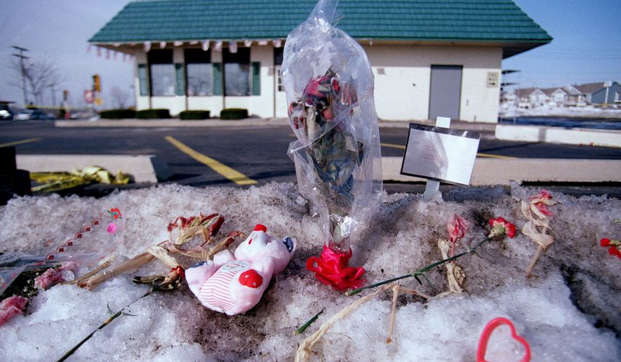 FILE - In this 1993 file photo memorials including flowers, signs, Valentine hearts and stuffed  teddy bears are place outside the Brown's Chicken & Pasta in Palatine, Ill., after seven people were murdered there on January 8, 1993. For the past 25 years, owner Frank Portillo Jr.'s thoughts at this time of year have been with those seven people. (Dave Tonge/Daily Herald via AP File)