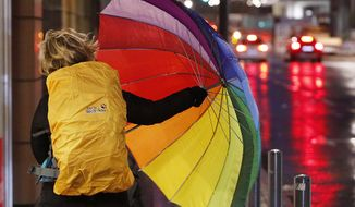 A woman fights with her colorful umbrella as she walks in the city center of Frankfurt, Germany, on a stormy Thursday, Jan. 18, 2018. Heavy storms are forecasted for most parts of Germany on Thursday. (AP Photo/Michael Probst)