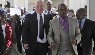 FILE - In this May, 10, 2010, file photo, Roy Bennett, center left, leaves the High Court in Harare, Zimbabwe, after he was acquitted of terrorism charges. New Mexico State Police said Thursday, Jan. 18 2018, that Zimbabwean opposition leader Roy Bennett died in helicopter crash. The crash on Wednesday, Jan. 17, carrying Bennett and five others went down in a mountainous rural area of northern New Mexico. (AP Photo/Tsvangirayi Mukwazhi, File)