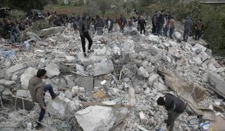 People look through the rubble of the house of Palestinian gunman Ahmed Jarrar following Israeli military operations in the West Bank city of Jenin, Thursday, Jan. 18, 2018. Israeli police say special forces killed a Palestinian gunman in the West Bank who allegedly killed an Israeli in a drive-by shooting earlier this month. (AP Photo/Majdi Mohammed)