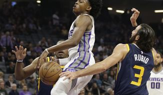 Sacramento Kings guard De'Aaron Fox, left, has the ball hit out of his hands by Utah Jazz guard Ricky Rubio during the first quarter of an NBA basketball game Wednesday, Jan. 17, 2018, in Sacramento, Calif. (AP Photo/Rich Pedroncelli)