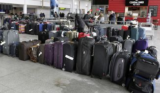 FILE - In this Jan. 8, 2018, file photo, unclaimed baggage sits at New York's John F. Kennedy Airport after a water pipe burst following several days of weather-related delays in the wake of a powerful winter storm. Over a week after winter weather woes snowballed into a long weekend of dysfunction at the airport, some passengers are still waiting for their baggage. The still-missing luggage is a fraction of the thousands of unclaimed bags that accumulated during the chaos. (AP Photo/Richard Drew, File)