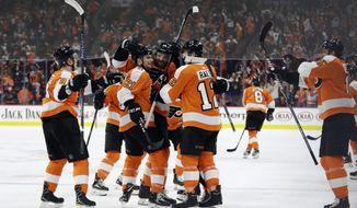 Philadelphia Flyers' Sean Couturier (14) celebrates with Scott Laughton (21), Michael Raffl (12), Ivan Provorov (9) and Jori Lehtera (15) after Couturier scored the winning goal during overtime in an NHL hockey game, Thursday, Jan. 18, 2018, in Philadelphia. (AP Photo/Matt Slocum)