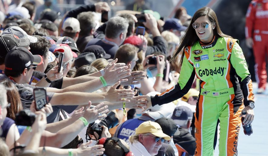 FILE - In this Feb. 22, 2015, file photo, driver Danica Patrick greets fans as she is introduced before the start of the Daytona 500 NASCAR Sprint Cup series auto race at Daytona International Speedway in Daytona Beach, Fla. GoDaddy tells The Associated Press it is partnering with Patrick as she closes her career with the Daytona 500 and the Indianapolis 500. (AP Photo/John Raoux, File) **FILE**