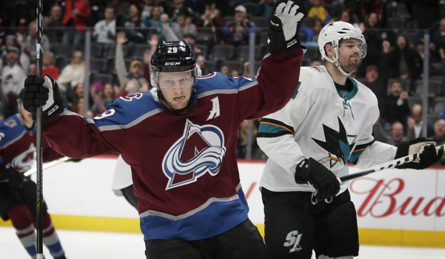 Colorado Avalanche center Nathan MacKinnon (29) celebrates his goal as San Jose Sharks defenseman Marc-Edouard Vlasic (44) skates away in the first period of an NHL hockey game in Denver on Thursday, Jan. 18, 2018. (AP Photo/Joe Mahoney)