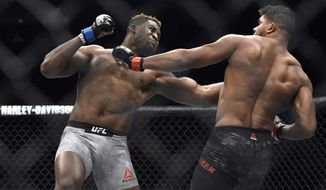 FILE- In this Dec. 2, 2017, file photo, Francis Ngannou, left, hits Alistair Overeem in the first round during a UFC 218 heavyweight mixed martial arts bout, in Detroit. Ngannou defeated Overeem by first-round knockout. Ngannou has knockout power that snaps heads back like Pez dispensers and earned him comparisons to Mike Tyson in his ferocious heyday. Ngannou will compete in the heavyweight champion bout against Stipe Miocic in the main event of UFC 220. (AP Photo/Jose Juarez, File)