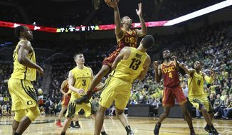 Southern California's Jordan McLaughlin drives to the basket against Oregon players, including MiKyle McIntosh, left, Payton Pritchard and Paul White (13), with USC's Chimezie Metu and Oregon's Troy Brown Jr. watching at right during the second half of an NCAA college basketball game Thursday, Jan. 18, 2018, in Eugene, Ore. Referees first called a foul on White, but reversed the call to a player control foul on McLaughlin. (AP Photo/Chris Pietsch)