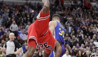 Chicago Bulls' Kris Dunn gets upside down after a dunk over Golden State Warriors' Stephen Curry during the second half of an NBA basketball game Wednesday, Jan. 17, 2018, in Chicago. The Warriors won 119-112. Dunn was injured on the play. (AP Photo/Charles Rex Arbogast)