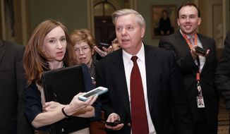 Sen. Lindsey Graham, R-S.C., front right, walks as he is questioned by reporters on Capitol Hill, Friday, Jan. 19, 2018, in Washington. (AP Photo/Alex Brandon)