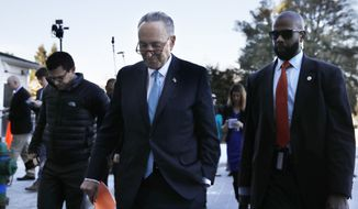 Senate Minority Leader Chuck Schumer, D-N.Y., center, returns to the Capitol after meeting with President Donald Trump, Friday, Jan. 19, 2018, in Washington. (AP Photo/Jacquelyn Martin)