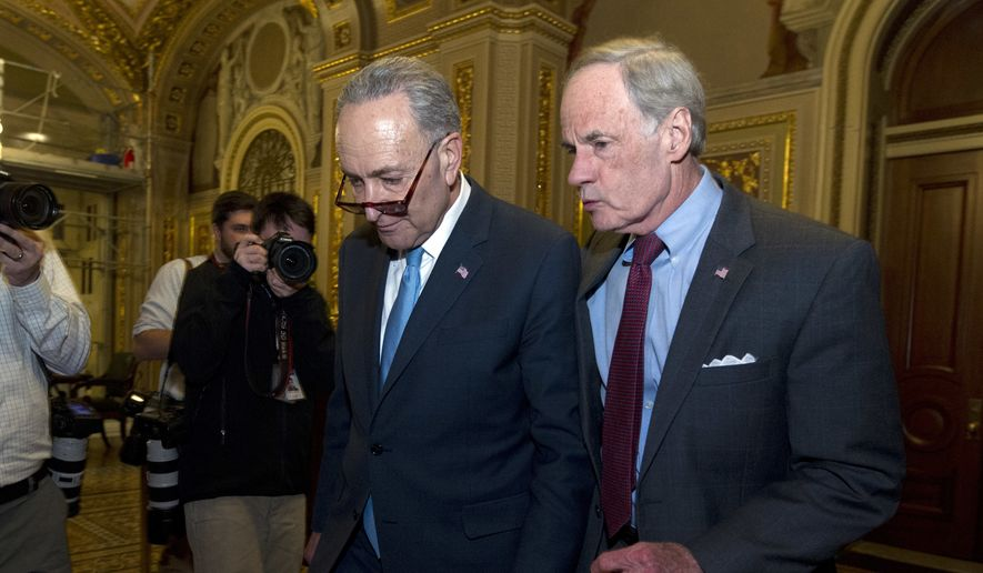 Sen. Charles Schumer, D-N.Y., left, speaks with Sen. Tom Carper D-Del. after a closed democrats meeting on Capitol Hill, Friday, Jan. 19, 2018, in Washington. ( AP Photo/Jose Luis Magana)