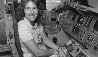 FILE - In this Sept. 13, 1985 file photo, Christa McAuliffe tries out the commander's seat on the flight deck of a shuttle simulator at the Johnson Space Center in Houston, Texas. Thirty-two years after the Challenger disaster, a pair of teachers turned astronauts on the International Space Station will pay tribute to McAuliffe by carrying out her science classes. (AP Photo)