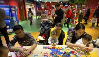 In this Dec. 23, 2017 photo, parents and children play together at an activity station during the grand opening of a Hamleys toy store in Beijing. The birthrate in China fell in 2017 despite the country easing family limits and allowing all couples to have two children. (AP Photo/Mark Schiefelbein)