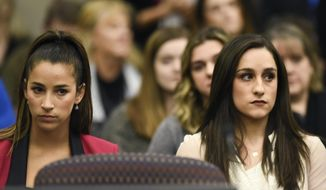 Former Olympians Aly Raisman, left, and Jordyn Wieber sit in Circuit Judge Rosemarie Aquilina's courtroom during the fourth day of sentencing for former sports doctor Larry Nassar, who pled guilty to multiple counts of sexual assault, Friday, Jan. 19, 2018, in Lansing, Mich. (Matthew Dae Smith /Lansing State Journal via AP) **FILE**