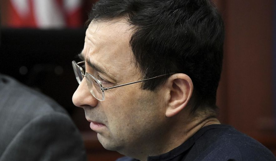 Larry Nassar listens to Jordyn Wieber's impact statement in the court of Judge Rosemarie Aquilina on Friday, Jan. 19, 2018, in Lansing, Mich., during the fourth day of sentencing for the former sports doctor, who pled guilty to multiple counts of sexual assault. (Dale G. Young/Detroit News via AP)
