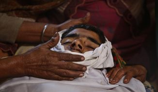 Relatives of Indian boy Sahil kumar who was killed in Pakistani firing and shelling, wail near his body at a hospital in  Ranbir Singh Pura district of Jammu and Kashmir, India, Friday, Jan.19,2018. Tensions soared along the volatile frontier between India and Pakistan in the disputed Himalayan region of Kashmir as soldiers of the rivals continued shelling villages and border posts for third day Friday. (AP Photo/Channi Anand)