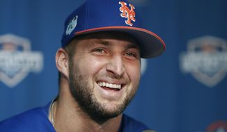 FILE - In this Feb. 27 2017, file photo, New York Mets outfielder and former NFL quarterback Tim Tebow laughs during a news conference at the baseball teams spring training facility in Port St. Lucie, Fla. Tebow will attend major league spring training with the New York Mets. The 30-year-old outfielder was among nine spring training invitees announced by the team Friday, Jan. 19, 2017. (AP Photo/John Bazemore, File)