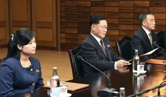 FILE - In this Jan. 15, 2018, file photo, in this photo provided by South Korea Unification Ministry, the head of North Korean delegation Kwon Hyok Bong, center, and Hyon Song Wol, the head of the Moranbong Band, left, sit during the meeting with South Korea at the North side of Panmunjom in North Korea. The head of North Korea's most popular girl band is visiting South Korea this weekend to check preparations for a trip by another Northern art troupe led by her as part of Pyongyang's Olympic delegation, officials said Friday.(South Korea Unification Ministry via AP, File)