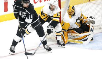 Los Angeles Kings forward Anze Kopitar, left, vies with Pittsburgh Penguins forward Riley Sheahan, center, for the puck during an NHL hockey game in Los Angeles on Thursday, Jan. 18, 2018. (AP Photo/Ringo H.W. Chiu)