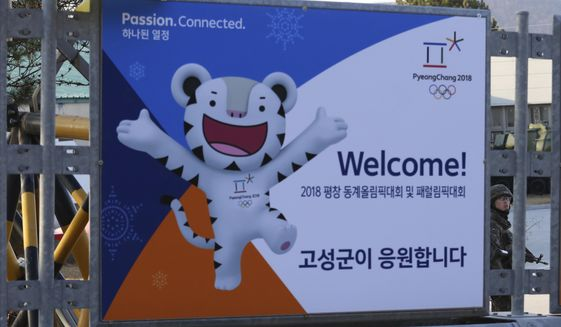 A South Korean army soldier stands guard behind a poster showing the 2018 Pyeongchang Winter Olympic mascot at the Unification Observation post in Goseong, near the border with North Korea, South Korea, Friday, Jan. 19, 2018. The rival Koreas agreed Wednesday to form their first unified Olympic team and have their athletes parade together for the first time in 11 years during the opening ceremony of next month's Winter Olympics in South Korea, officials said. (AP Photo/Ahn Young-joon)