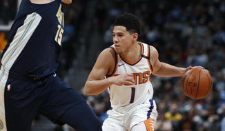Phoenix Suns guard Devin Booker, right, drives the lane past Denver Nuggets center Nikola Jokic during the second half of an NBA basketball game Friday, Jan. 19, 2018, in Denver. Phoenix won 108-100. (AP Photo/David Zalubowski)