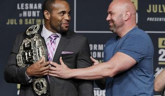 FILE - In this July 6, 2016, file photo, Dana White, right, President of the Ultimate Fighting Championship, holds back Daniel Cormier during a UFC 200 mixed martial arts news conference in Las Vegas. Cormier is pumped to defend his UFC light heavyweight championship and says he can beat Volkan Oezdemir. They will fight at UFC 220 on Jan. 20, 2018, in Boston. (AP Photo/John Locher, File)