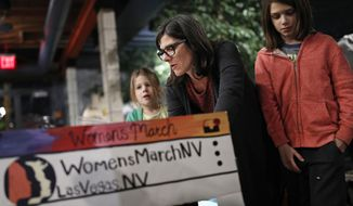 In this Jan. 17, 2018, photo, Minnie Wood, center, makes signs with her daughters Buckley, right, and Zoey in preparation for a rally in Las Vegas. A year after more than 1 million people rallied at women's marches around the world with a message of female empowerment and protest of President Donald Trump, organizers will mark the anniversary with more than a hundred marches around the world and a rally in Las Vegas aiming to channel the activism to register voters and swing elections for progressives this year. (AP Photo/John Locher)