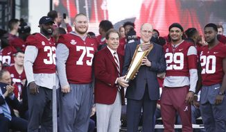 Alabama head coach Nick Saban holds up the National Championship trophy during the NCAA college football national championship celebration, Saturday, Jan. 20, 2018, in Tuscaloosa, Ala. Alabama won the national championship game against Georgia 26-23 in overtime. (AP Photo/Brynn Anderson)