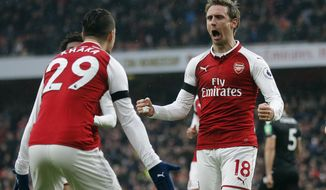 Arsenal's Nacho Monreal, center, celebrates with teammates after scoring his side's first goal during the English Premier League soccer match between Arsenal and Crystal Palace at the Emirates stadium in London, Saturday, Jan. 20, 2018.(AP Photo/Frank Augstein)