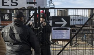 """A United States Park Police officer, center, locks a gate leading to a Statue of Liberty ferry, Saturday, Jan. 20, 2018, in New York. The National Park Service announced that the Statue of Liberty and Ellis Island would be closed Saturday """"due to a lapse in appropriations."""" Late Friday, the Senate failed to approve legislation to keep the government from shutting down after the midnight deadline. (AP Photo/Mary Altaffer)"""