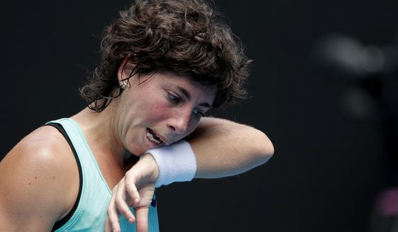 Spain's Carla Suarez Navarro wipes sweat from her face during her fourth round match against Anett Kontaveit of Estonia at the Australian Open tennis championships in Melbourne, Australia, Sunday, Jan. 21, 2018. (AP Photo/Vincent Thian)