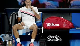 Switzerland's Roger Federer eats a snack bar during a break in his third round match against France's Richard Gasquet at the Australian Open tennis championships in Melbourne, Australia, Saturday, Jan. 20, 2018. (AP Photo/Vincent Thian)