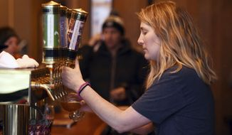 In this Jan. 4, 2018, photo, Erin Krueger pours a pitcher of their Ski Socks American Sour at the Great Northern Brewing Company in Whitefish, Mont. (Brenda Ahearn/The Daily Inter Lake via AP)