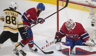 Boston Bruins' David Pastrnak (88) scores against Montreal Canadiens goaltender Carey Price as Canadiens' Jordie Benn defends during the third period of an NHL hockey game in Montreal, Saturday, Jan. 20, 2018. (Graham Hughes/The Canadian Press via AP)